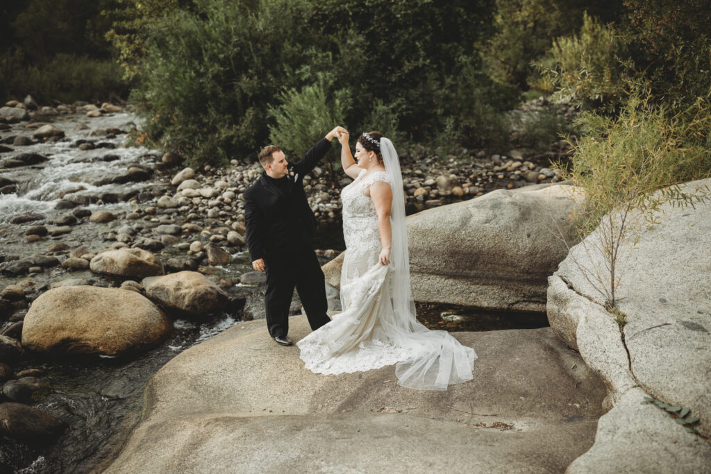 Beautiful couple on wedding day in nature on rocks in waterfall in nature dancing lace wedding dress and cathedral length veil and black tux