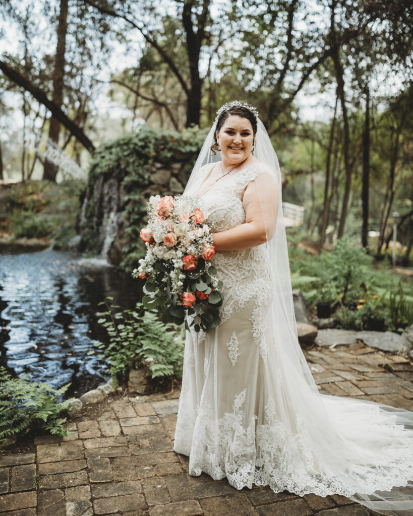Beautiful plus size bride on wedding day smiling with lace dress in nature by waterfall in long beach califorfnia