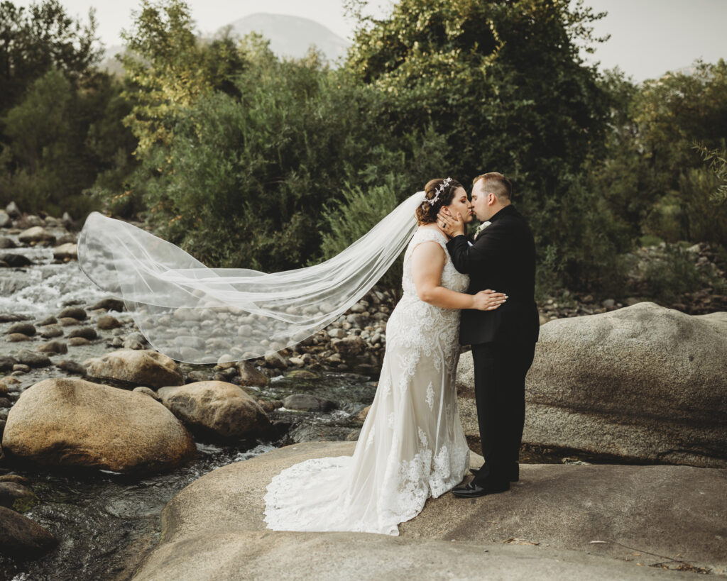 Wedding day couple on rocks in nature kissing lace dress black tux