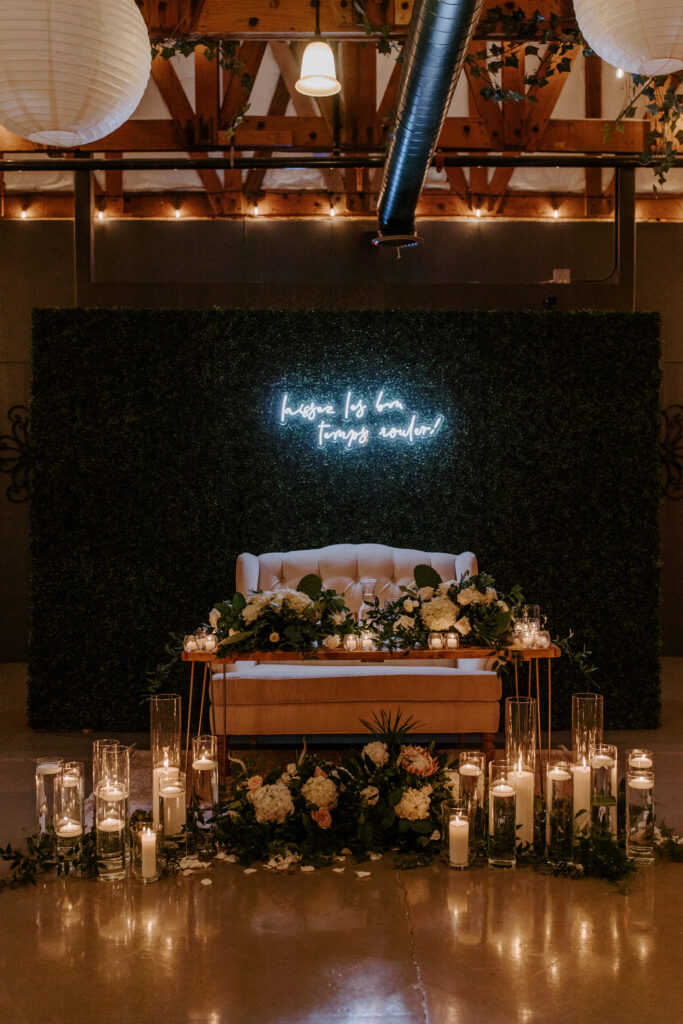 sweetheart table with couch at indoor wedding reception