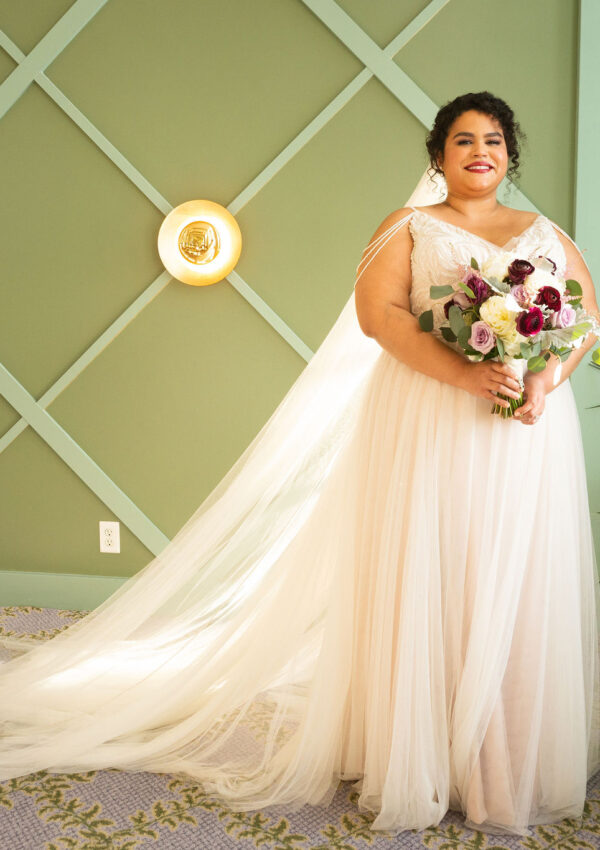 plus size bride wearing flowy wedding dress in front of green wall