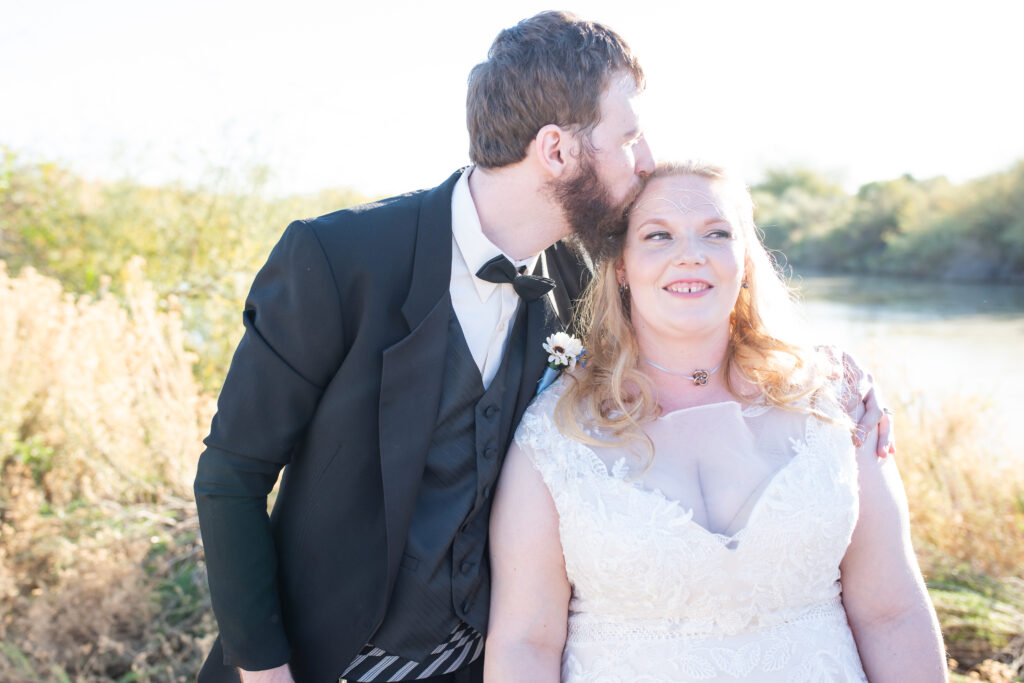 plus size bride with groom tux kissing her head