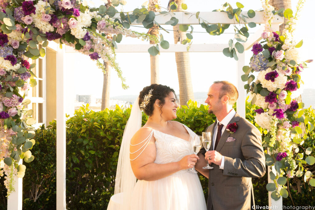 couple toasting under floral arch
