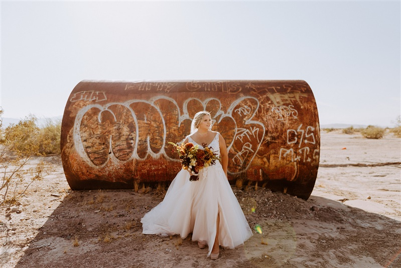 plus size bride in gown stnding in front of water thing with grafitti