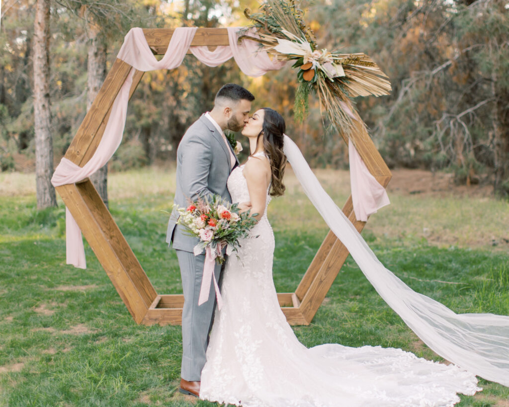 outdoor wedding with geometric wood arch