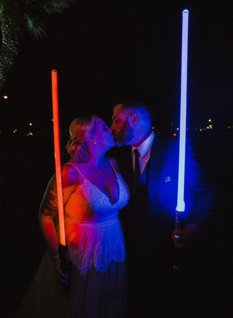 newlyweds holding light sabres