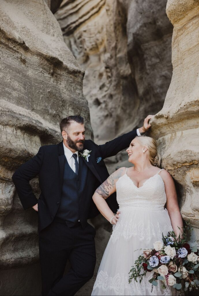 bride and groom infront of interesting rock wall