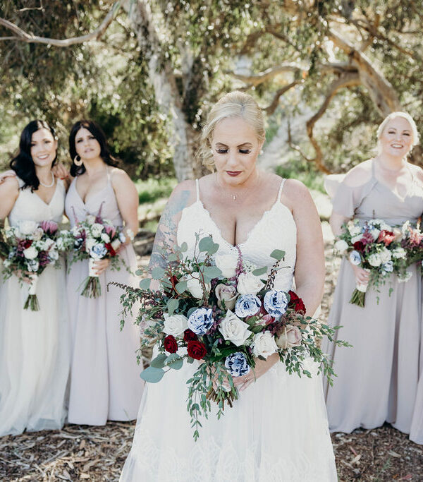 bride holding wedding bouquet with bridesmaids behind her