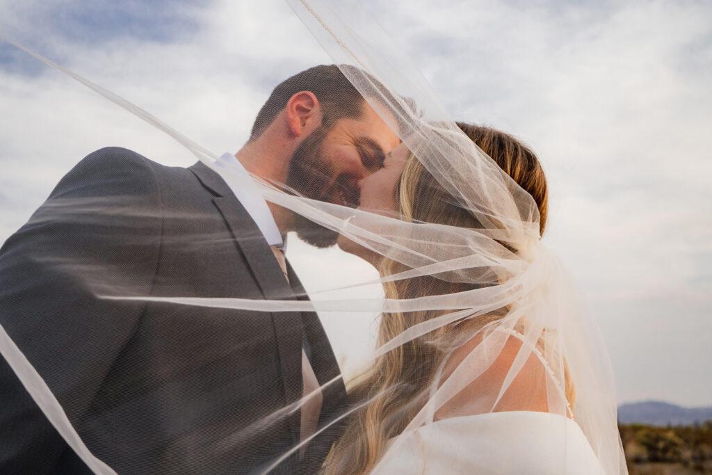 bride and groom kissing behind wedding veil