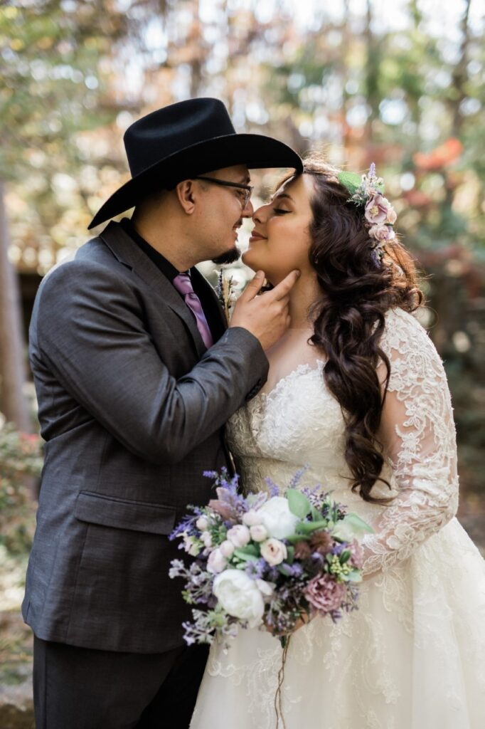 bride and groom kissing, he wears a hat, she holds a bouquet