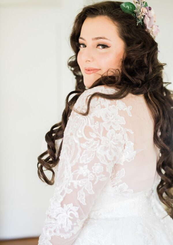 gorgeous long brown haired bride with long sleeve wedding dress