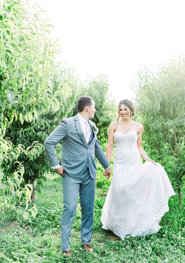bride in wedding dress and groom in tux in green field