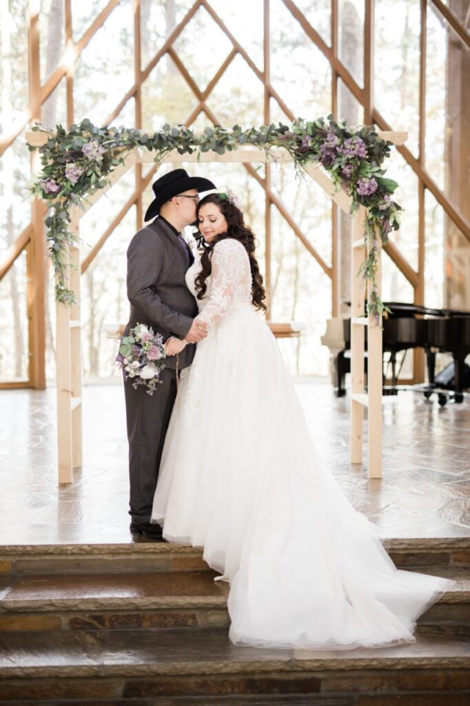 bride and groom inside wedding venue with wooden arch