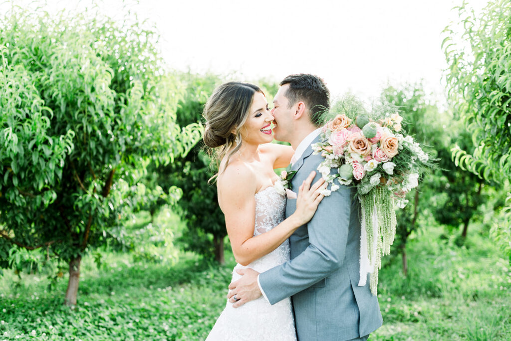 bride and groom with large bouquet with green trees arizona