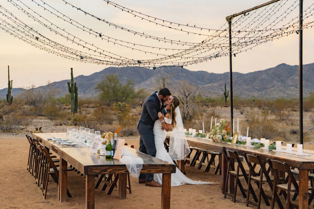 couple kissing under lights at rutic outdoor wedding venue