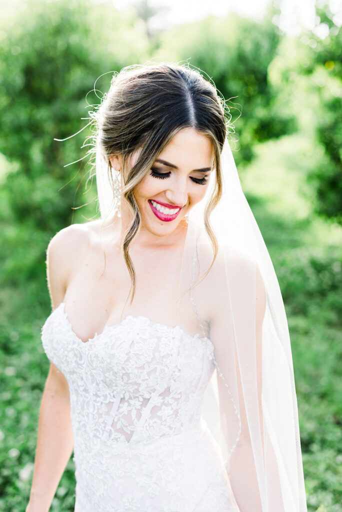 bride wearing veil and strapless lace wedding dress