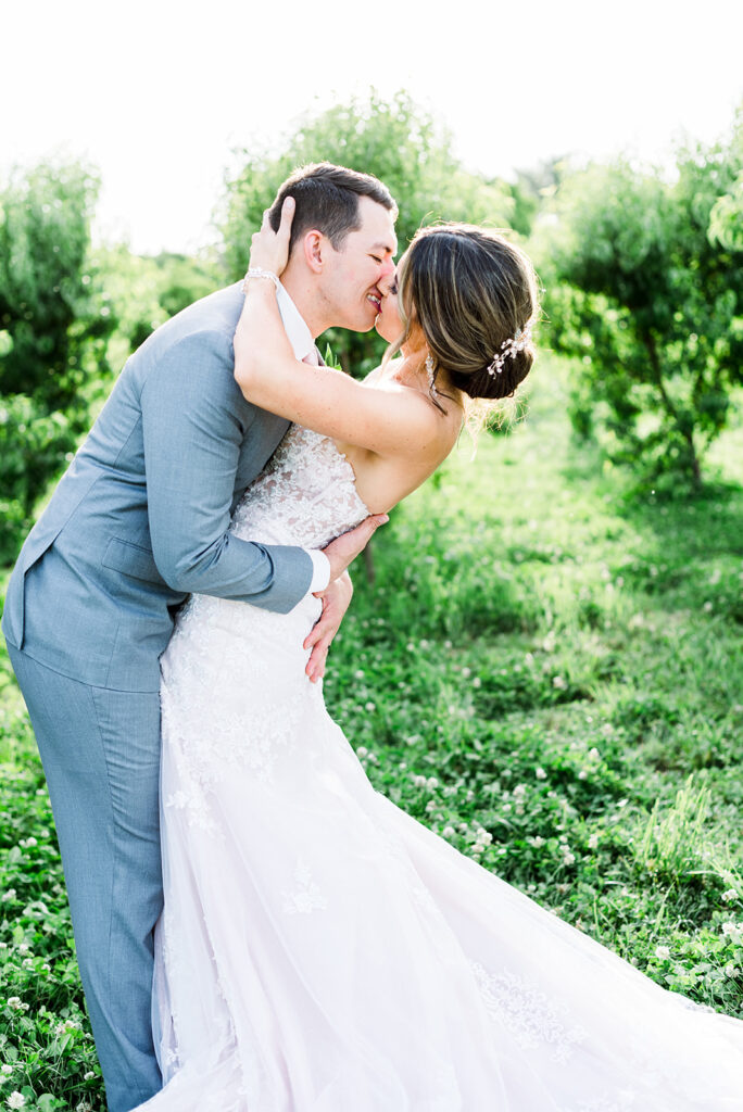 bride and groom kissing with green trees arizona