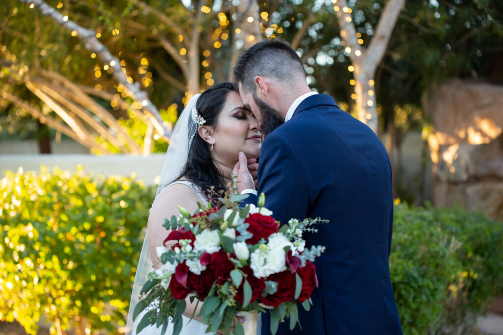 bride and groom with bride holding large floral bouquet