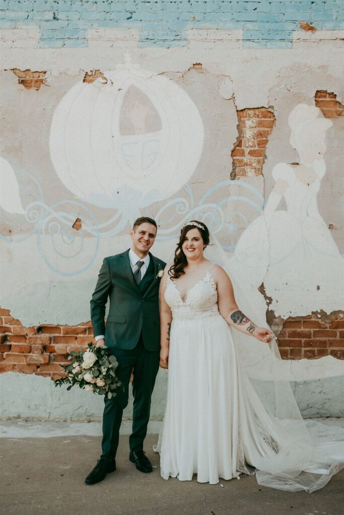 bride and groom in front of cinderella mural