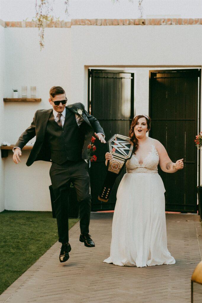 bride and groom carrying wrestling belt