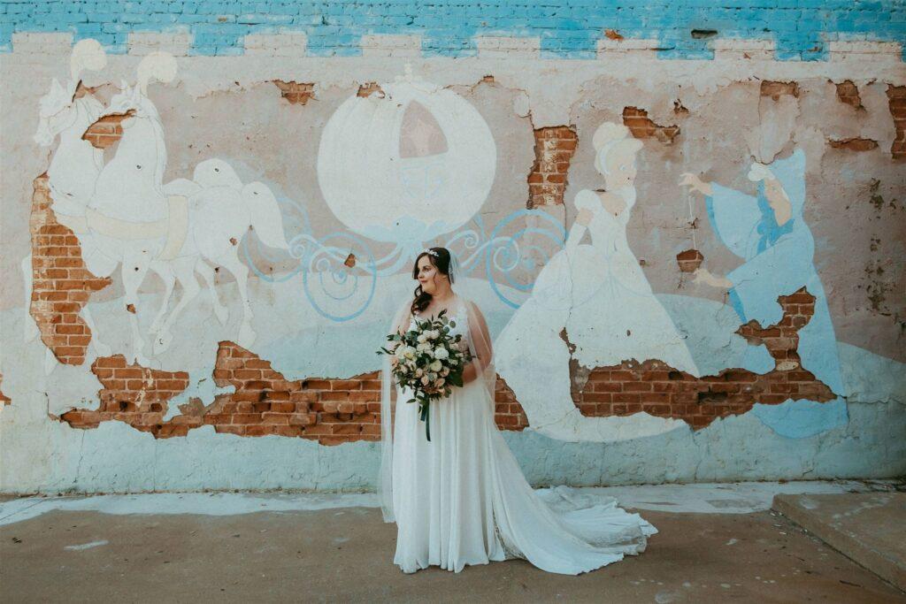 real plus size bride in front on cinderella mural mesa arizona