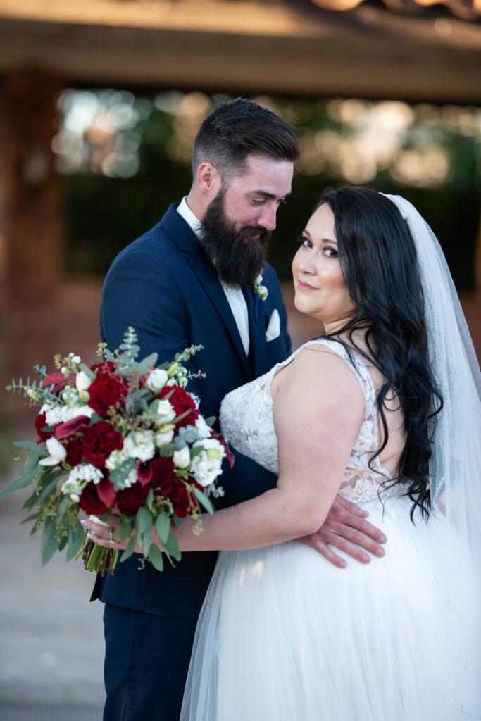 groom with bride looking over her shoulder holding bouquet