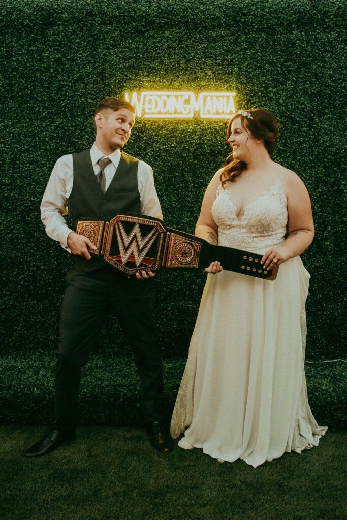 bride and groom holding a wrestling belt
