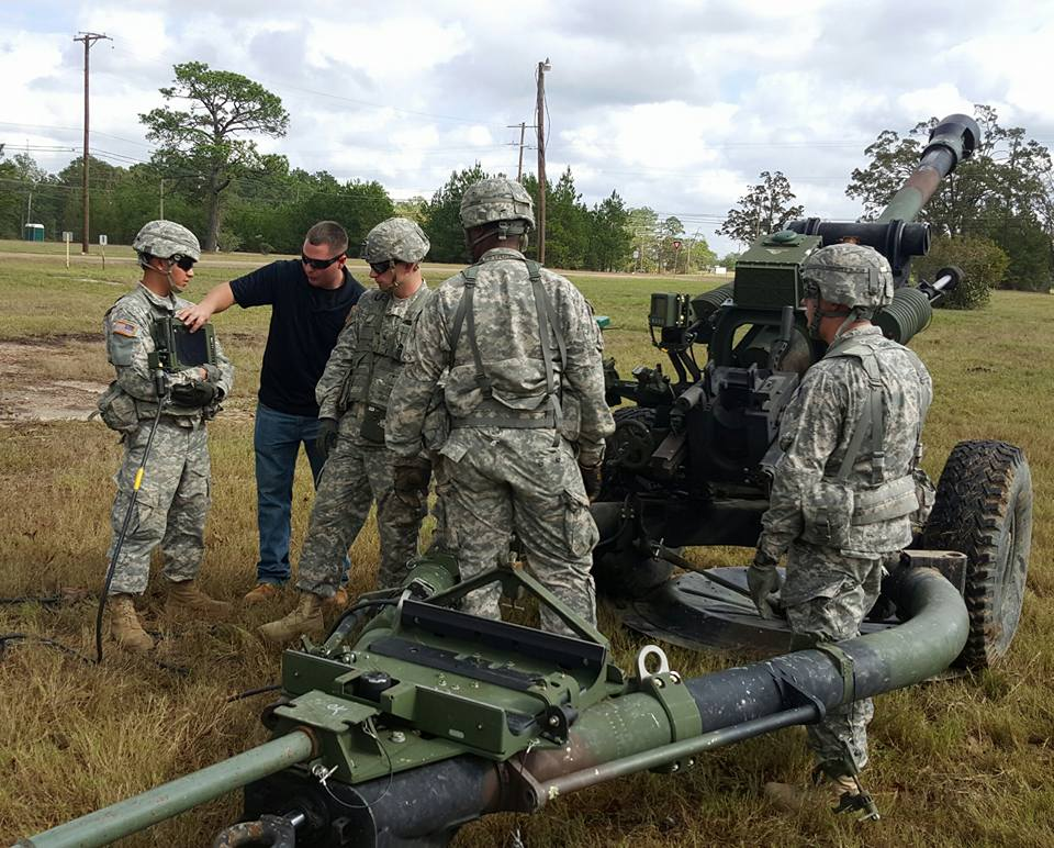Tec-Masters Inc. Mathew Bailey provides instruction to the M119A3 Howitzer Section Chief on the how to properly utilize the Fire Control Computer (FCC) for  processing digital fire mission data received from the Fire Direction Center (FDC)