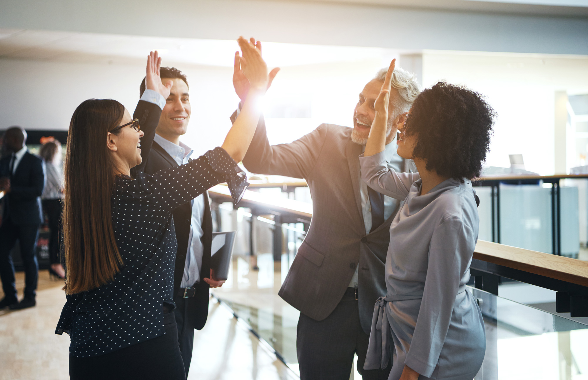 Diverse group of smiling businesspeople high fiving each other while standing together in a corridor of a modern office building