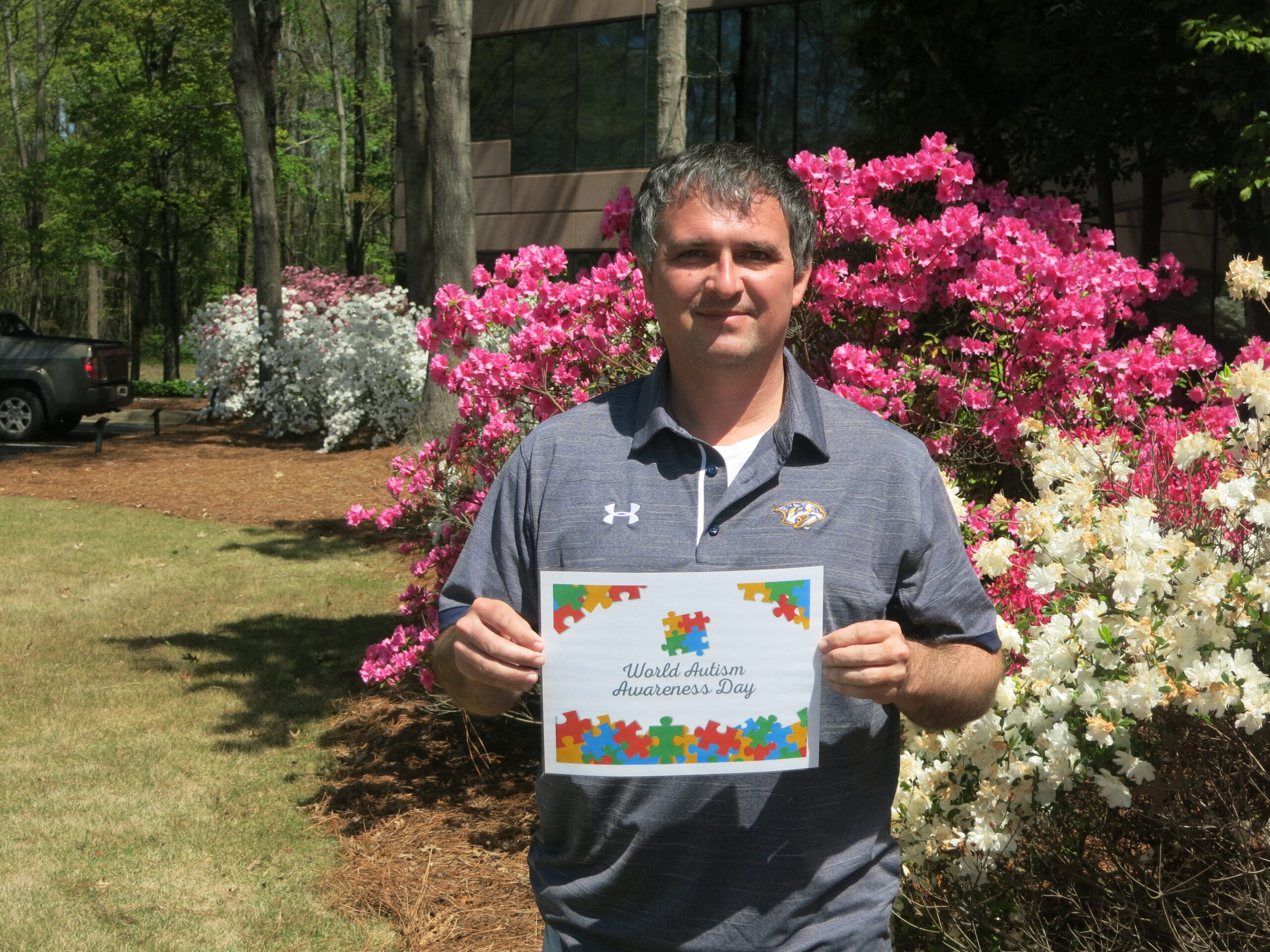 Tec-Masters' employee Andrew Isbell holding a sign of encouragement for our Autism walk.