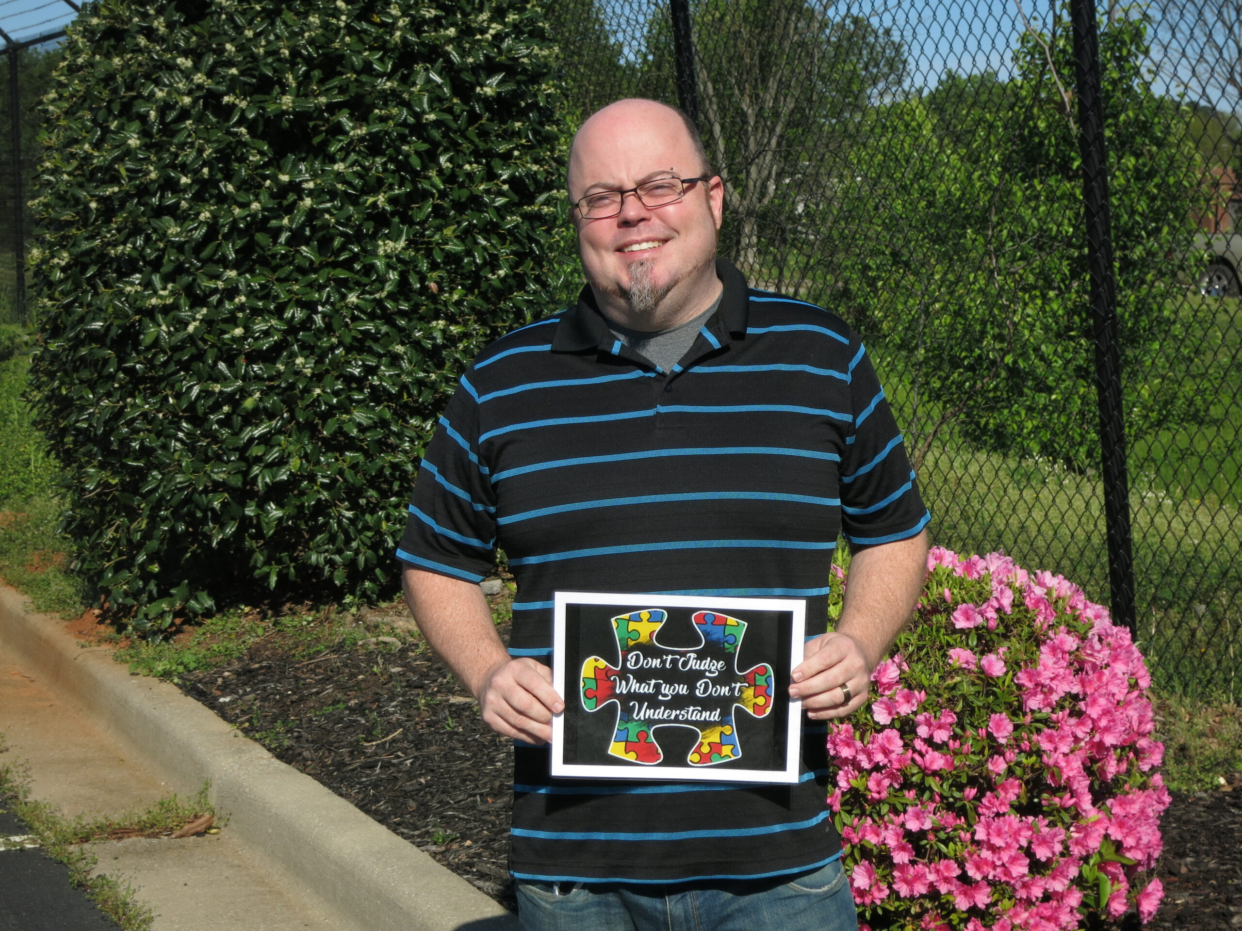 Tec-Masters' employee holding a sign of encouragement for our Autism walk.