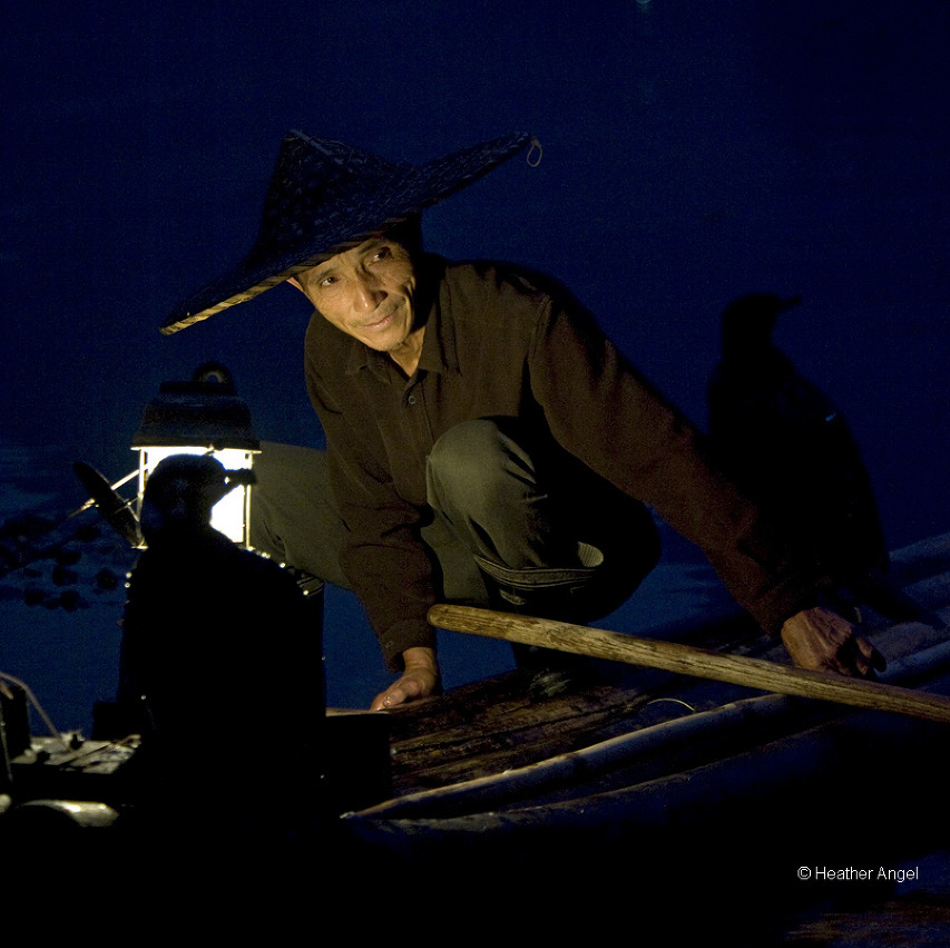 Cormorant fisherman lit by the light of his hurricane lamp on the Lijiang, China