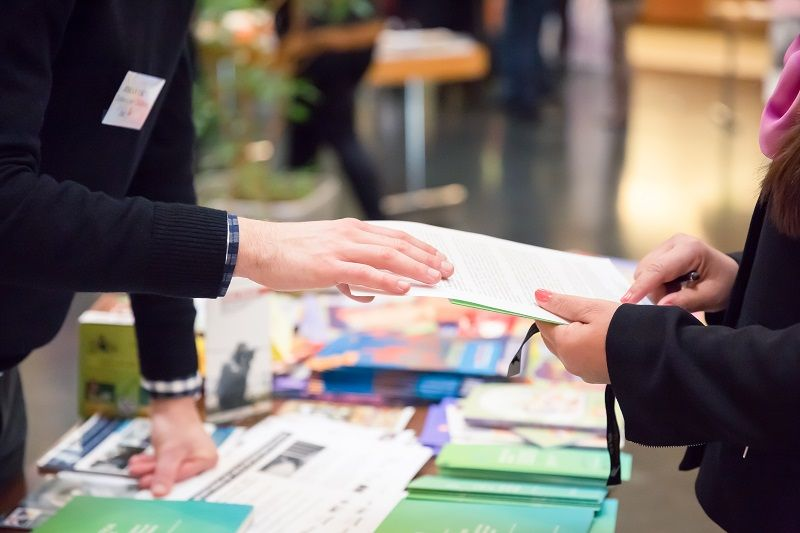 Man-and-Woman-Sharing-Information-Leaflet-over-Exhibition-Stand-cm