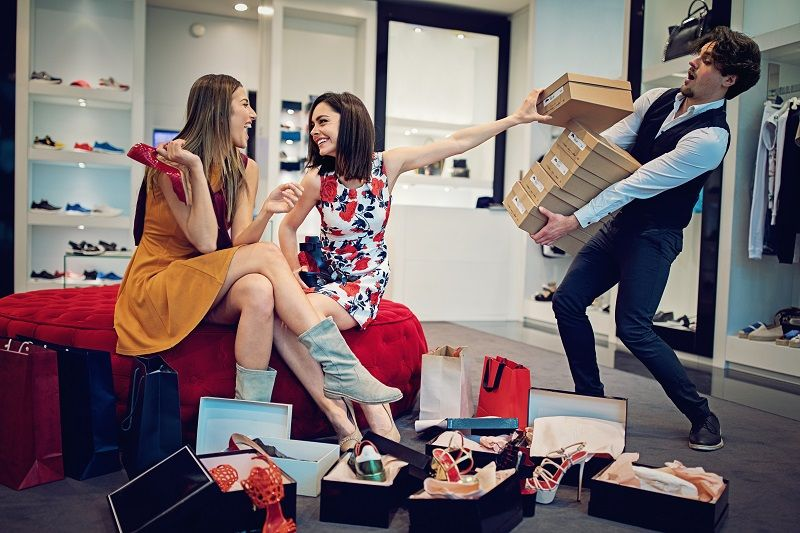 Shopping-girls-are-choosing-shoes-and-asking-from-salesman-for-more-cm