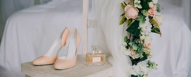 Bridal-accessories-on-a-white-chair-with-flowers,-perfume-shoes-cm