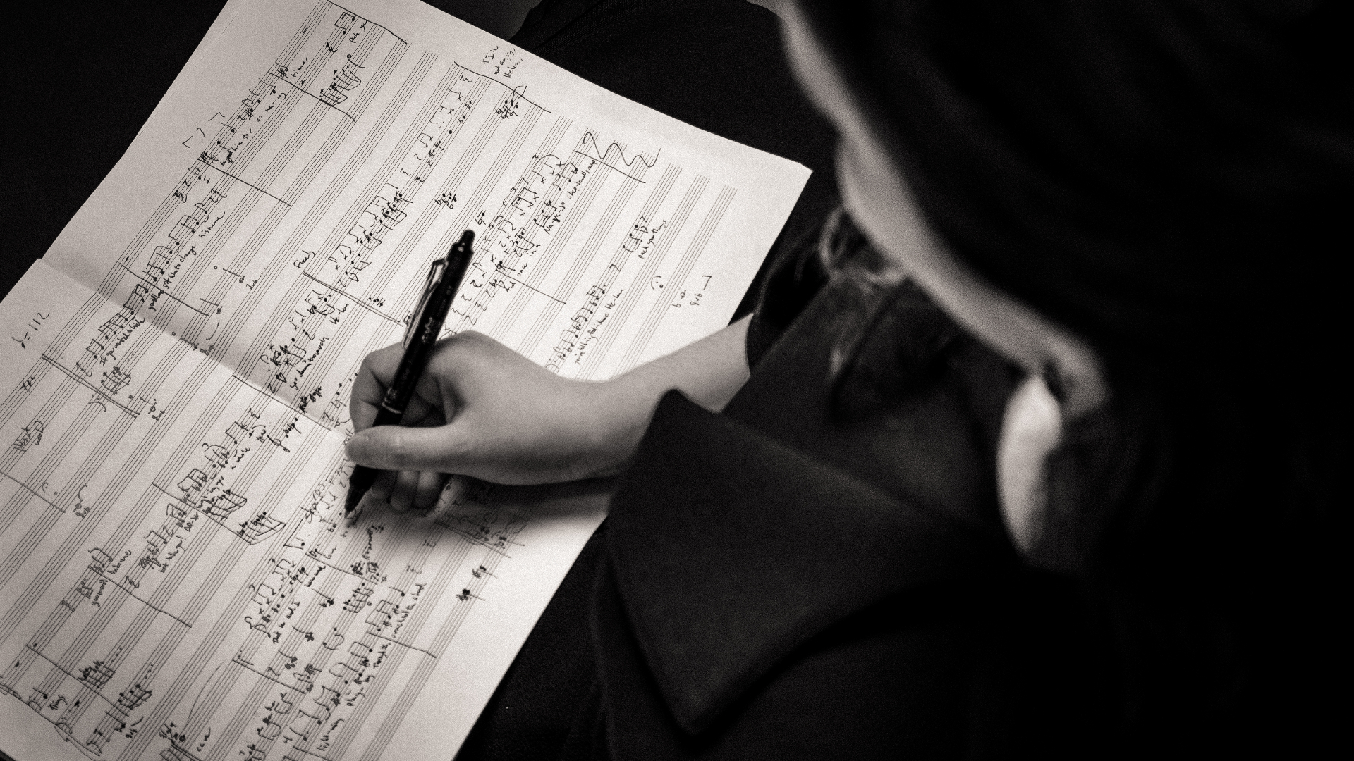 Abstract photograph of Jessica Hunt's hand as she writes music notation