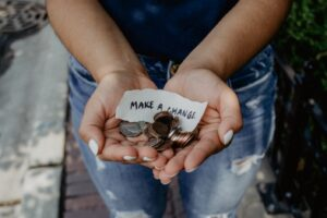 "A woman holds change with a note saying ""make a change"""