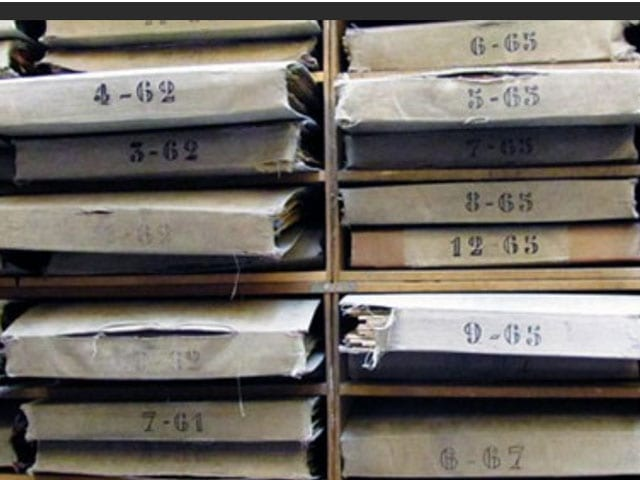 Photo of archival folders with numbers and letters