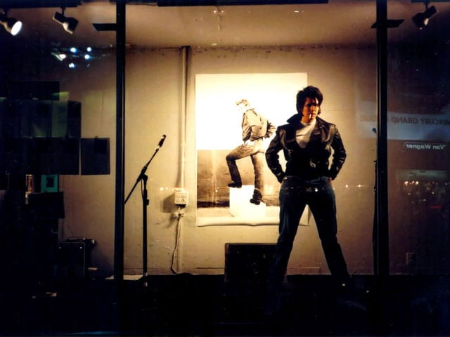 Photo of A.L Steiner dressed in leather standing in storefront window