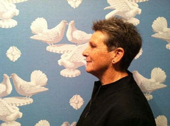 photo of Tirza Latimer in front of wallpaper of doves