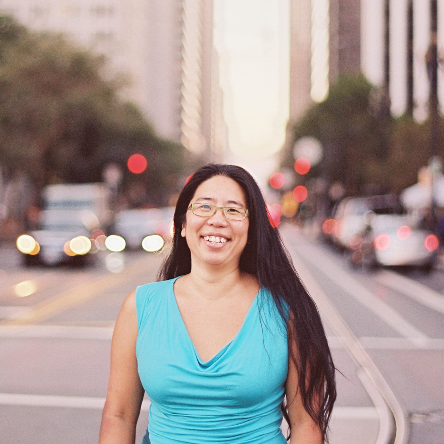 Long haired smiling person with glasses standing on a city street