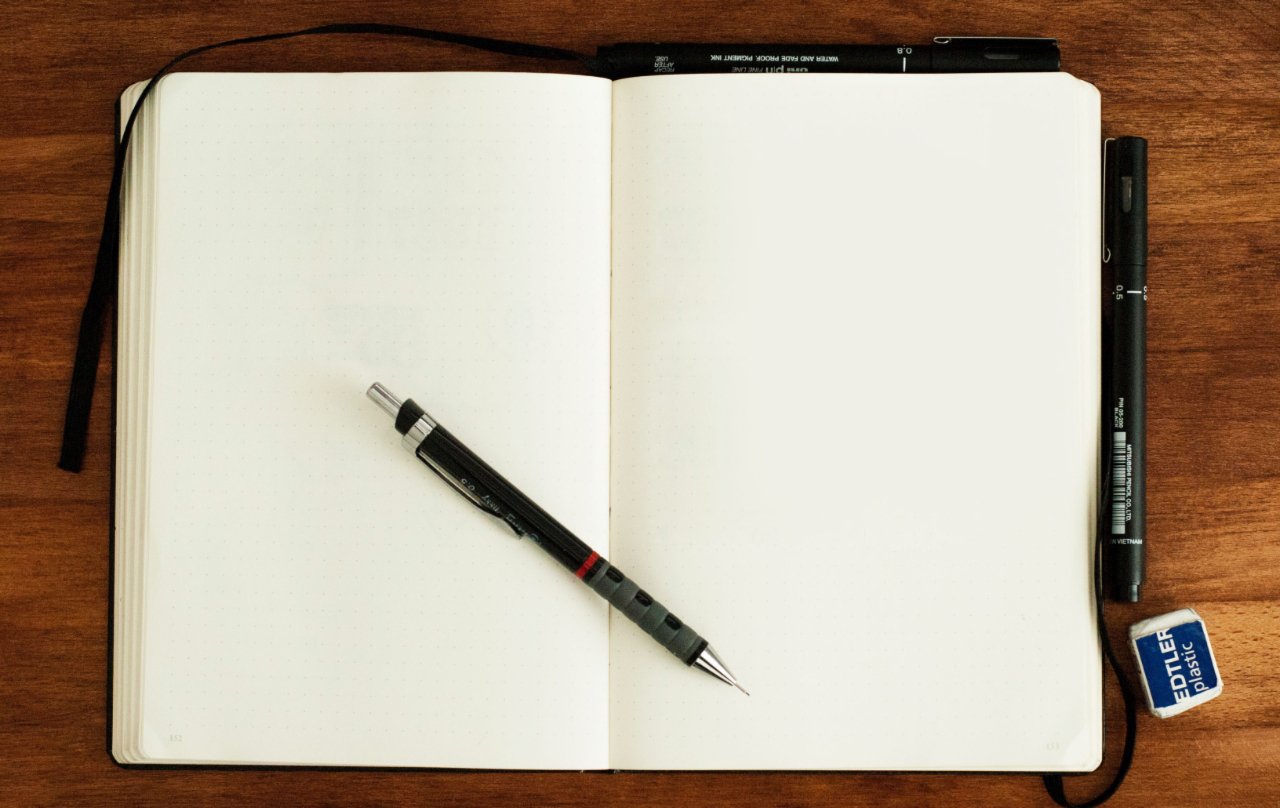 Blank pages of open notebook with black pens sitting across the notebook