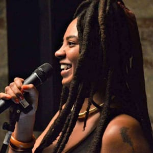 Profile photo of a brown skinned person with long dreads speaking into the microphone and smiling