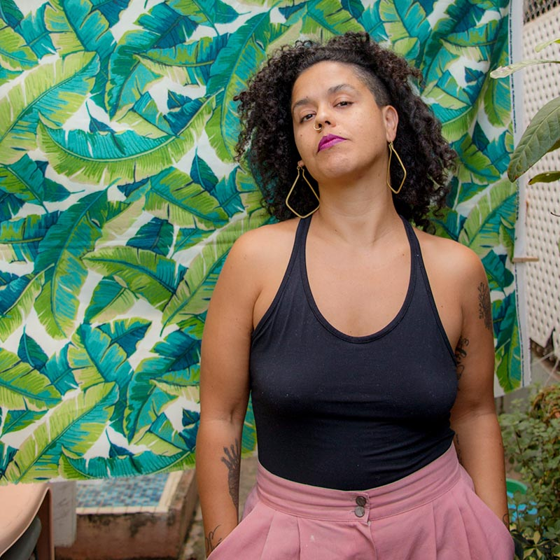 Curly haired brown skin person with pink pants, black leotard, hoop earrings standing against a colorful background