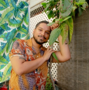 Brown skinned person leaning against a plant with short dark hair, beard, and mustache looking thoughtfully at the camera