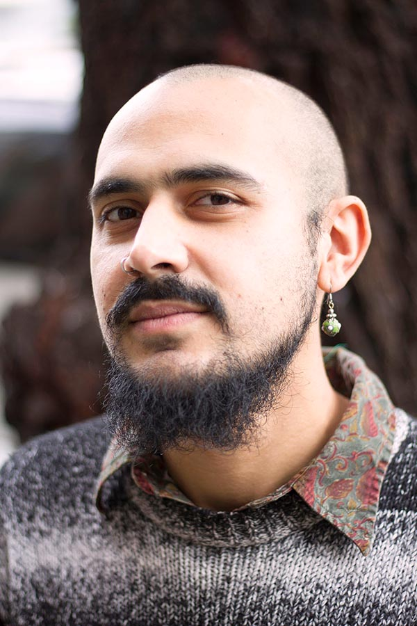 Bald headed person with beard, mustache, and one earring wearing a collared paisley shirt and knitted sweater
