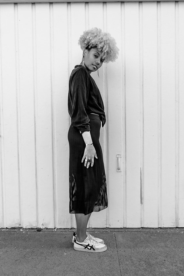 black and white photo of an athleisure outfit-thrift shirt-trendy skirt-livecgothesminded-fit femme
