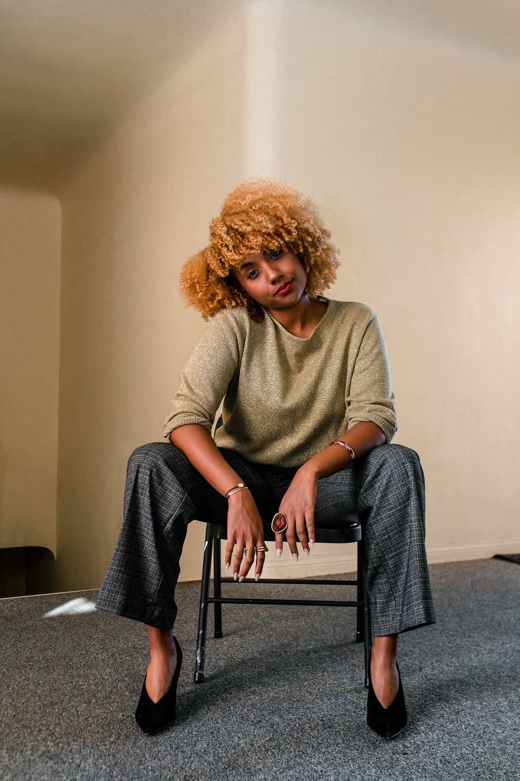 reflect -black woman with blonde curly hair wearing a work outfit