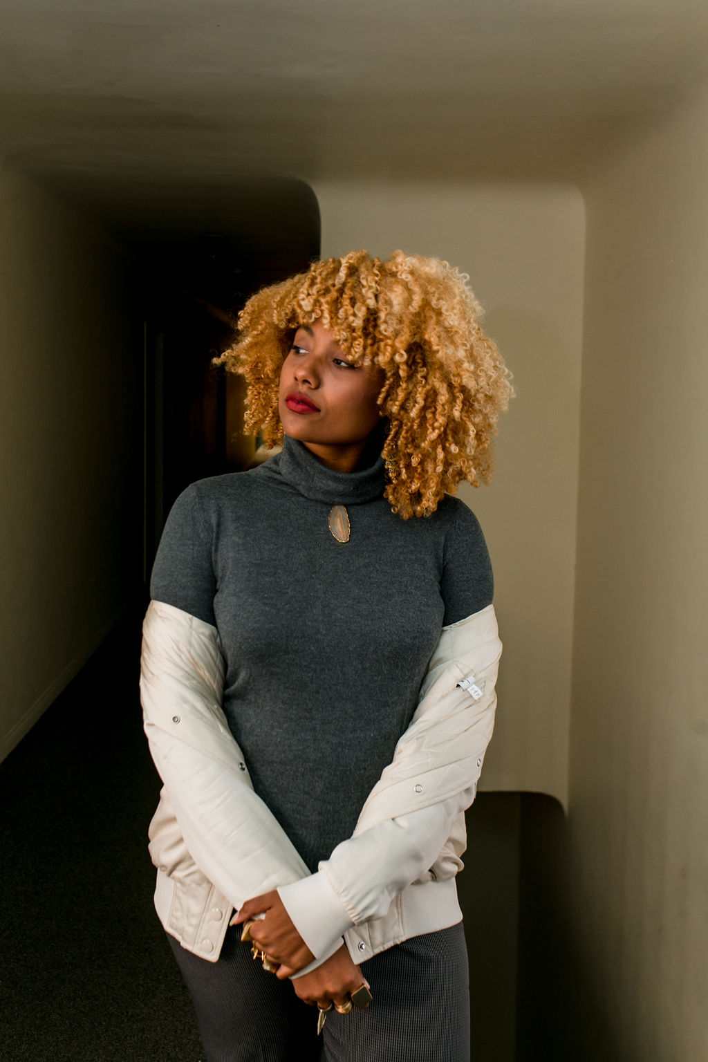 woman with blonde curly hair wearing a white bomber jacket