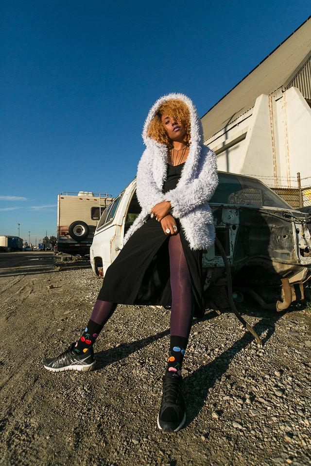 a girl wearing happy socks and faux fur coat
